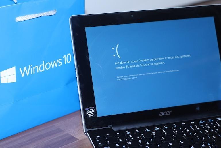 Titelbild des Artikels. Es zeigt einen Windows 10 Notebook, der gerade einen Bluescreen darstellt. Dahinter befindet sich eine Windows 10 Tüte für die Optik.