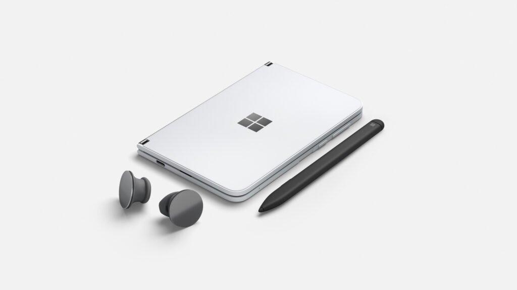 Surface Duo im zugeklappten Zustand, samt Surface Earbuds und Surface Pen
