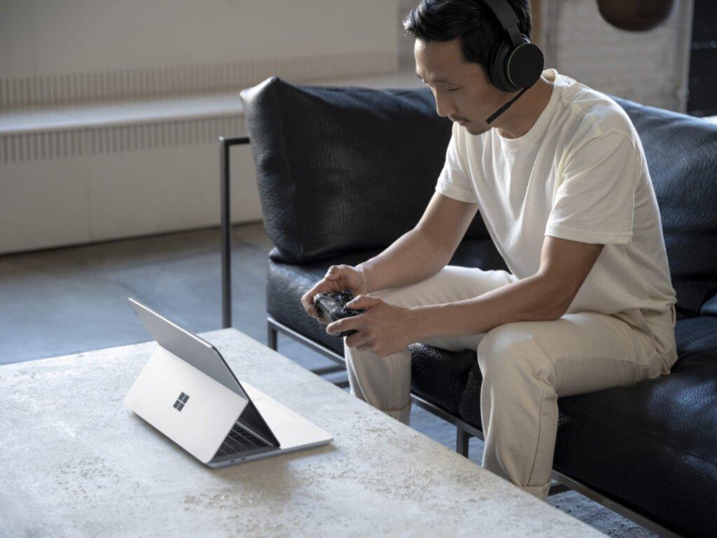 Das Surface Laptop auf dem Tisch mit geneigten Display, gegenüber von jemanden der darauf zockt.